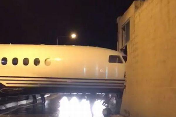 まさか!?ジェット機が風にあおられ、空港に隣接する建物の壁を突き破る