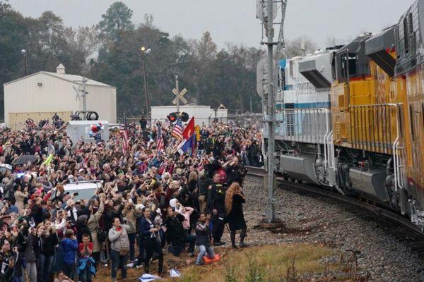 ブッシュ元大統領を見送るため、数千人が星条旗を手に線路沿いに集まる