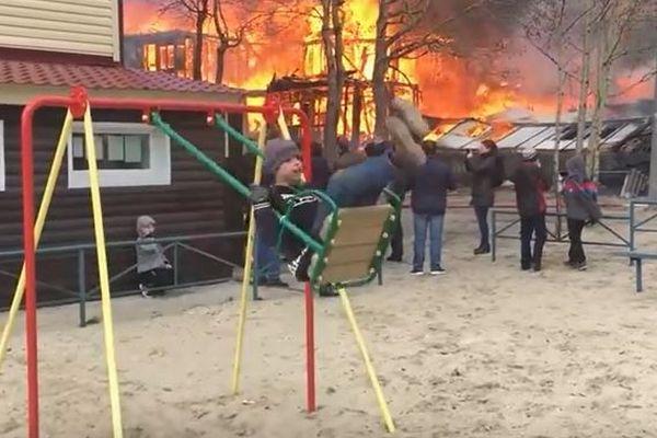 建物が燃えているそばで無邪気にブランコに乗る少年、その動画が注目を集める