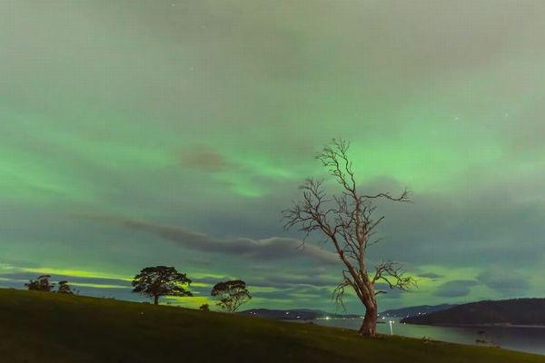 緑色の雲が浮かぶタスマニア島、オーロラの光が溶け込んだ風景が美しい