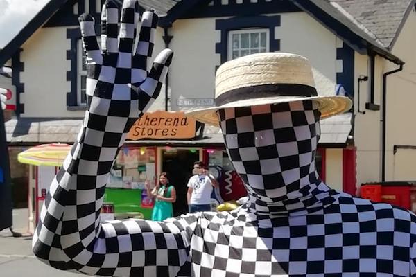 フェスティバルに現れた不思議なチェッカー模様男、注目とお金を集めて逃げ去る