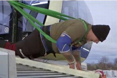 男性がロープで引っ張り、巨大な観覧車を回転させることに成功