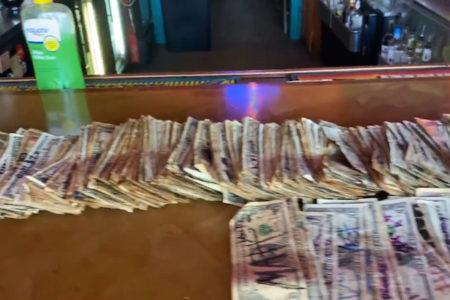 ロックダウンの中、バーオーナーが壁に貼られたドル紙幣で従業員に給料を