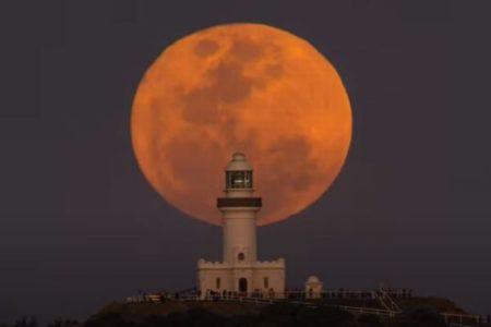 豪の岬に浮上した満月、赤く染まった「ハーベストムーン」の美しい映像