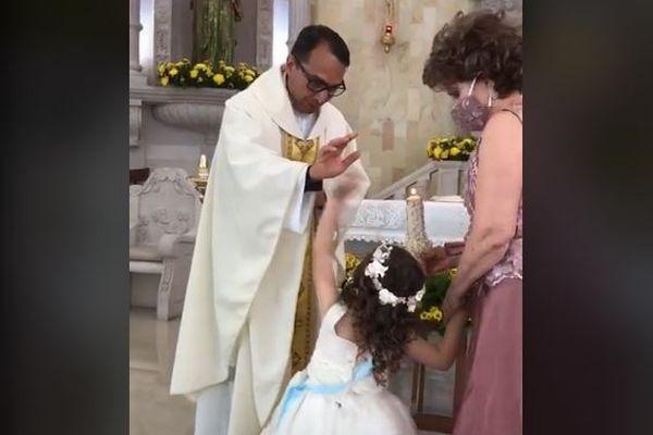 儀式で頭にかざした手に少女がハイタッチ、祝福する神父も笑いをこらえきれず