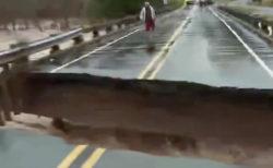 洪水のニュース放映中、レポーターの立つ橋が崩れた