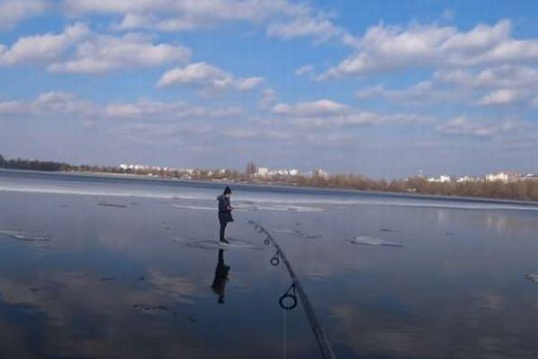 氷の上で流されていく少年、釣り人が竿を使い、リールを巻いて救助
