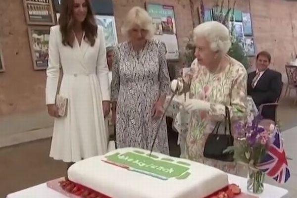 エリザベス女王が大きな剣でケーキカット、キャサリン妃も笑いを堪えきれず