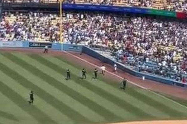ボール・ガールがお手柄!野球の試合中、グランドに侵入した男にタックル!