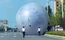 中国で巨大な月の風船が転がり、スタッフが懸命に追いかけていく