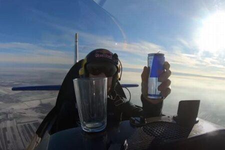 飛行中に「レッドブル」を飲みながら、機体を宙返りさせるパイロット